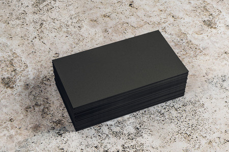 Empty black business card stack on concrete desktop. Info, address and message concept. Mock up, 3D Rendering Stock Photo