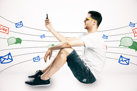 Side view of casual young guy sitting and using cellphone with communication sketch on subtle white background. Social network and media concept Banco de Imagens