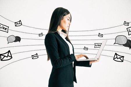 Side view of young businesswoman using laptop with communication sketch on white background. Social network and media concept Stock fotó