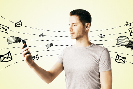 Side view of young guy using smartphone with communication sketch on subtle yellow background. Social network and media concept