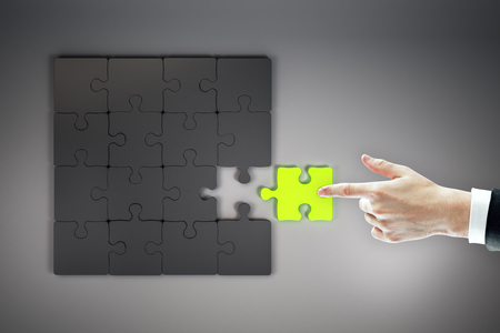 Top view of businessman hand assembling green jigsaw puzzle on grey background. Quiz and solution concept