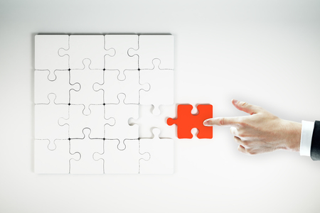 Top view of businessman hand assembling red jigsaw puzzle on white background. Quiz and solution concept Reklamní fotografie