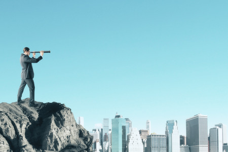 Side view of young businessman on cliff looking into the distance on blue sky background with city skyline and copy space. Research and vision concept