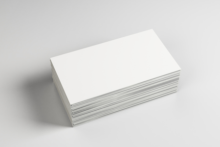 Empty white business card stack on light desktop. Info, address and message concept. Mock up, 3D Rendering