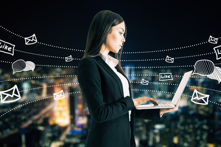 Side view of young businesswoman using laptop with communication sketch on blurry night city background. Social network and media concept