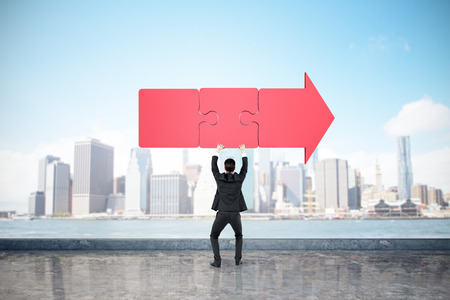 Back view of young businessman holding red puzzle arrow on bright blue sky and blurry city background. Direction and solution concept