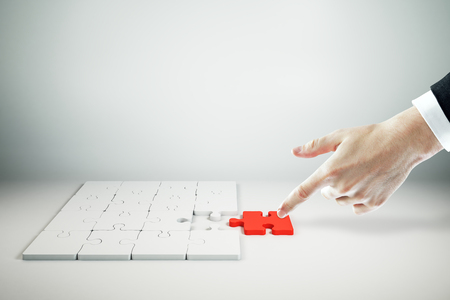Businessman hand assembling red jigsaw puzzle on white background. Quiz and solution concept