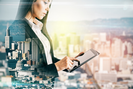 Pretty young european businesswoman using tablet on blurry city background. Communication and network concept. Double exposure