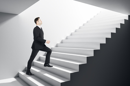 Businessman climbing concrete stairs in grey interior. Success and growth concept. Stok Fotoğraf