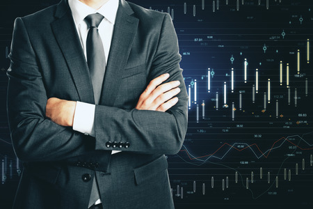 Trade and currency concept. Unrecognizable businessman with folded arms standing on dark background with forex chart