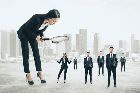 Attractive businesswoman with magnifier looking at businesspeople on blurry city background. Supervision and manager concept