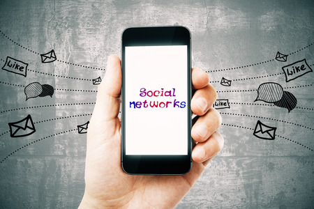 Hand holding smartphone with creative network sketch on concrete background. Social networking and media concept