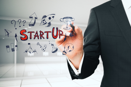 Businessman drawing creative start up sketch on blurry office interior background with reception desk. Startup and entrepreneur concept. Double exposure