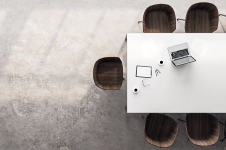 Top view of desktop with laptop, coffee cup and chairs in modern meeting room interior. 3D Rendering