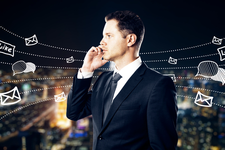 Side view of young businessman using smartpone with communication sketch on blurry night city background. Social network and media concept. Double exposure