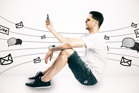 Side view of casual young guy sitting and using cellphone with communication sketch on subtle light background. Social network and media concept