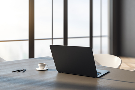 Close up and side view of laptop and coffee cup on wooden desk in office interior with panoramic city view and daylight. Toned image. 3D Rendering
