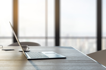 Close up and side view of laptop and coffee cup on wooden desk top in office interior with panoramic city view and daylight. Toned image. 3D Rendering