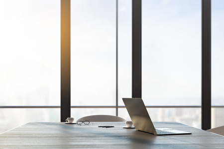 Close up and side view of laptop and coffee cup on wooden table in office interior with panoramic city view and daylight. Toned image. 3D Rendering