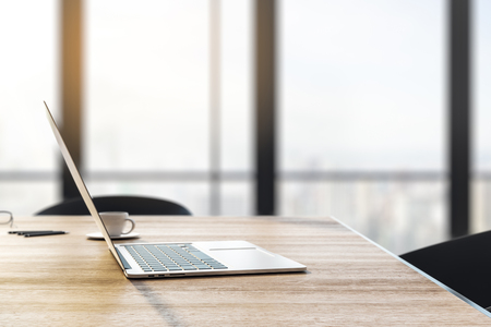 Close up and side view of laptop and coffee cup on wooden desktop in office interior with panoramic city view and daylight. Toned image. 3D Rendering