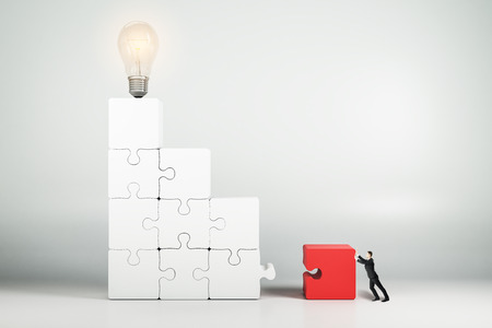 Businessman assembling jigsaw ladder with light bulb. Idea, quiz and solution concept.