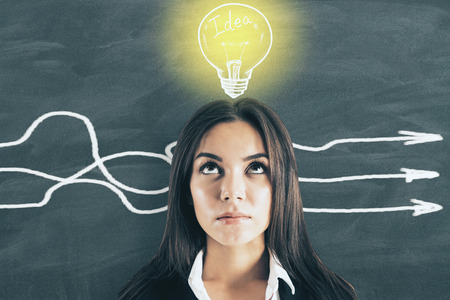 Portrait of attractive young european businesswoman with arrows and lamp sketch on chalkboard background. Idea and different direction concept Stock fotó