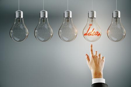 Hand wijzend op rij verlichte gloeilampen op subtiele achtergrond. Leiderschap, idee en keuzeconcept Stockfoto