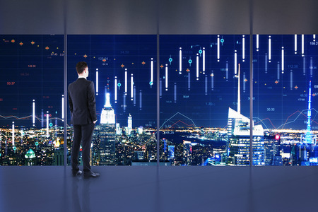Businessman standing in minimalistic office interior with night New York city view and forex chart on windows. Trade and stock concept. Multiexposure
