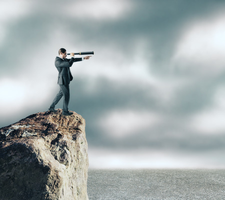 Side view of young businessman on cliff using binoculars to look into the distance. Sky and clouds background. Research and success concept