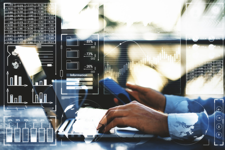 Side view of businessman hands using laptop and smartphone with business hologram on blurry outdoor background. Analytics and finance concept. Double exposure