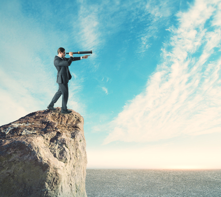Side view of young businessman on cliff using binoculars to look into the distance. Sky and clouds background. Research and vision concept