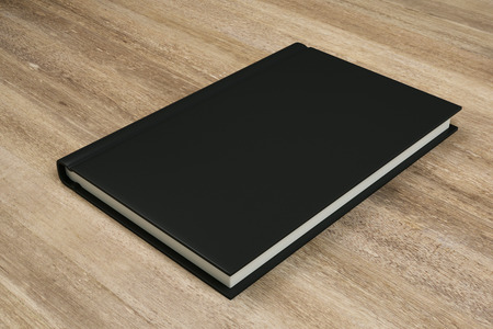Empty closed black hardcover book on wooden desktop background. Close up. Publish and info concept. Mock up, 3D Rendering Banco de Imagens