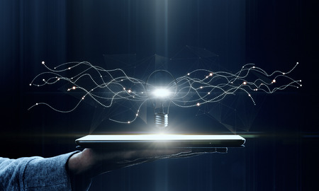 Hand holding tablet with creative glowing lamp on dark background. Idea and innovation concept