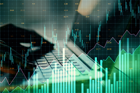 Close up of hands using laptop with glowing forex chart on blurry background. Invest and stats concept. Multiexposure