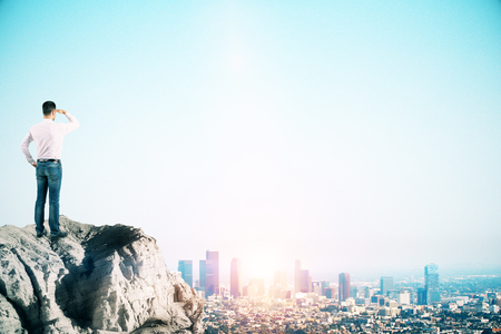Side view of young businessman looking into the distance on cliff with city skyline, copy space and sunlight. Research and vision concept Stok Fotoğraf - 123065425