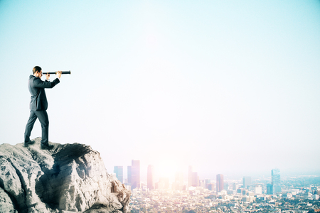 Young businessman on cliff looking into the distance on blue sky background with city skyline and copy space. Research and vision concept. Side view