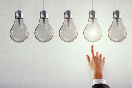 Hand pointing at row of illuminated light bulbs on subtle background. Leadership, idea and innovation concept 写真素材
