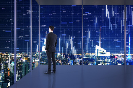 Businessman standing in minimalistic office interior with night New York city view and forex chart on windows. Trade and investment concept. Double exposure Stock Photo