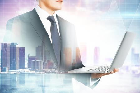 Vista laterale di attraente giovane uomo d'affari europeo utilizzando laptop su sfondo sfocato della città. Comunicazione e concetto di successo. Multiesposizione