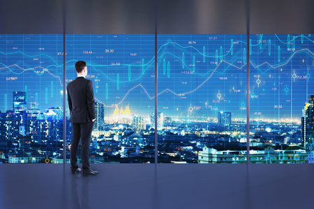 Businessman standing in minimalistic office interior with night New York city view and forex chart on windows. Trade and finance concept. Double exposure Stock Photo - 123066614