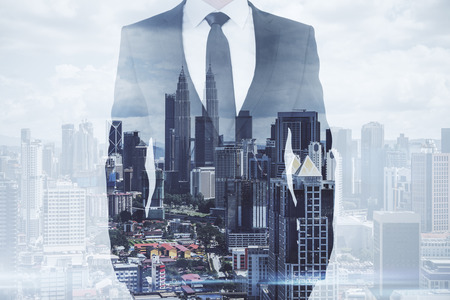 Businessman standing on creative Kuala Lumpur city background. Success and future concept. Double exposure
