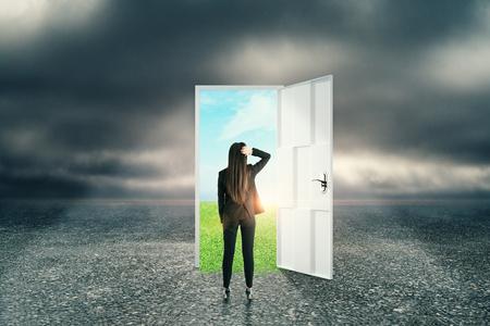 Femme d'affaires avec porte ouverte créative sur fond de paysage abstrait ciel extérieur. Succès et concept futur