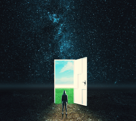 Back view of young person in hoodie looking at creative opportunity door on abstract outdoor sky landscape background. Success and dream concept
