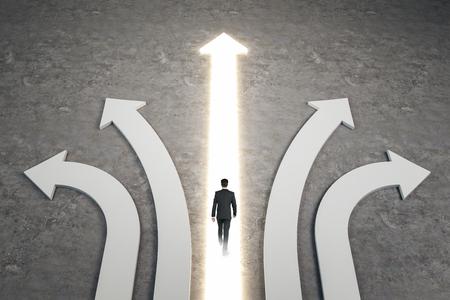 Geschäftsmann, der auf abstrakte weiße und leuchtende Pfeile auf konkretem Hintergrund geht. Unterschiedliche Richtung und Erfolgskonzept.
