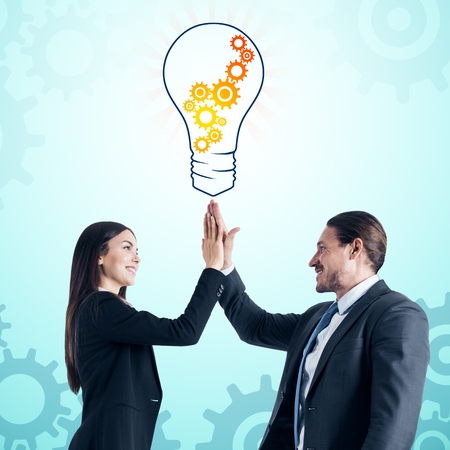 Attarctive young european businessman and woman giving hi-fives with creative cogwheel light bulb sketch on subtle white background. Idea, innovation and teamwork concept