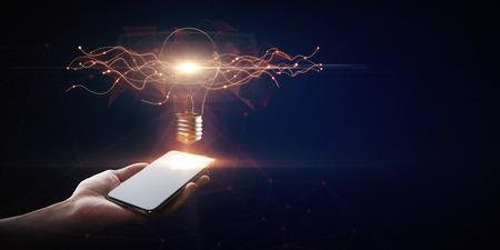Hand met smartphone met creatieve gloeiende lamp op donkere achtergrond. Idee en innovatieconcept Stockfoto