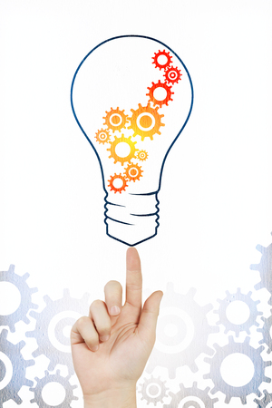 Hand pointing at creative cogwheel lamp sketch on subtle white background. Idea and machinery concept Stockfoto