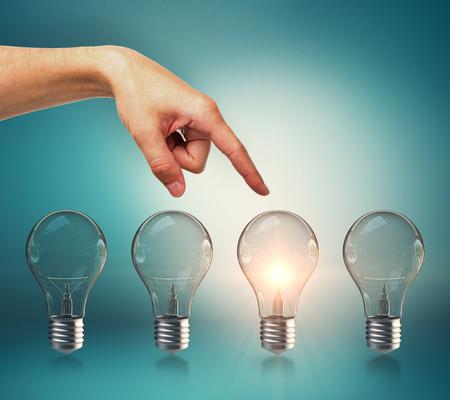 Female hand pointing at creative row of illuminated light bulbs. Choice, idea and leadership concept
