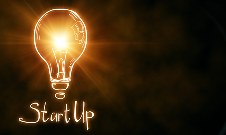 Creative glownig orange startup lamp on blurry background. Start up and idea concept. 3D Rendering