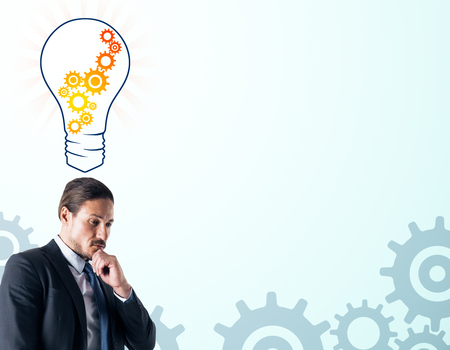 Attractive thoughtful young businessman with creative cogwheel light bulb sketch on subtle white background. Idea, innovation and machinery concept Banco de Imagens
